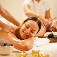 Young couple enjoying in back massage at health spa. Focus is on smiling woman.